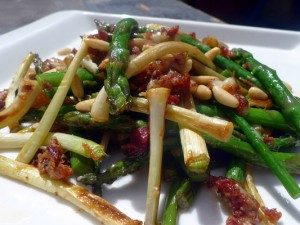 Sautéed asparagus and tender garlic sprouts with cured ham shoulder pieces
